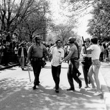Police arresting two students, circa 1960-1975.