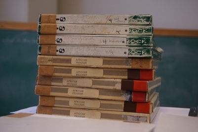 Photograph of audio reel boxes with titles of programs including