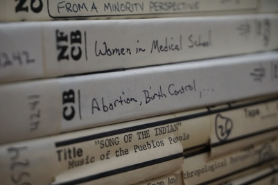 Photo of stack of audio reel boxes with titles including