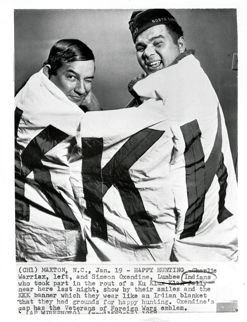 Charlie Warriax and Simeon Oxendine wrapped in KKK banner after shutting down a klan rally