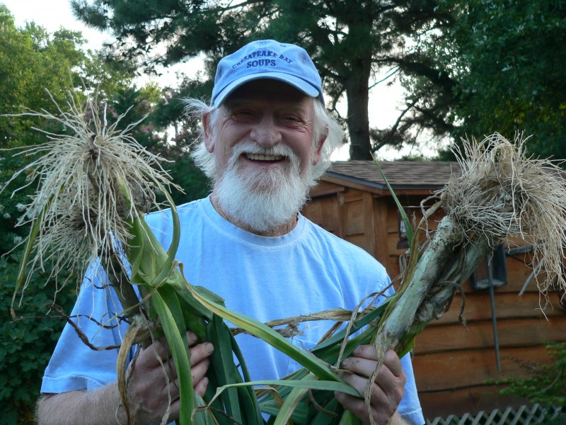 picture of Whitey Schmidt holding leeks from his garden
