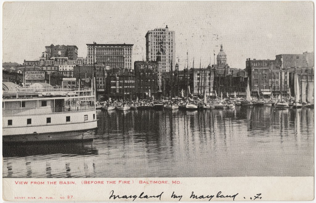 Black and white photograph of downtown Baltimore, taken from the water. Small sailboats float in front of the city skyline, which is dominated by a few large buildings and a series of brick structures.