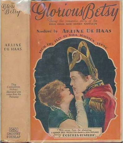 The dust jacket of a book entitled Glorious Betsy by Arline De Haas features a woman in a Dixie dress, Betsy, holding her finger up against a man dressed in French imperial clothing, Napoleon. The scene is set on a dark orange background.