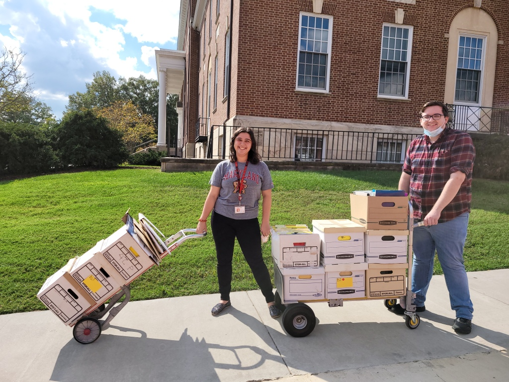 Susannah Holliday (left) and Matt LaRoche (right) stand outside on UMD's campus, each maneuvering a dolly stacked with several records boxes.